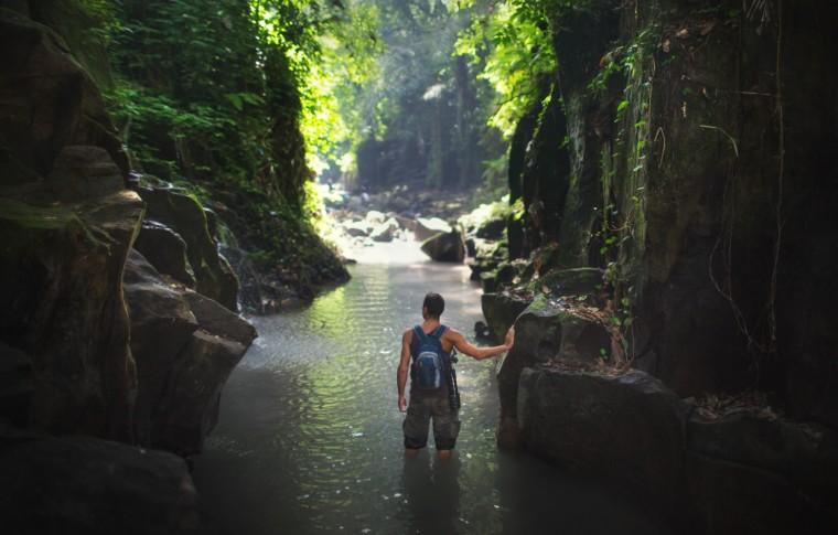 tourist walking through a river