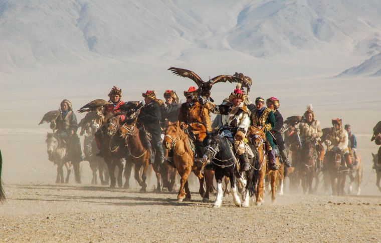 a group of mongolian eagle hunters following a golden eagle on their horses