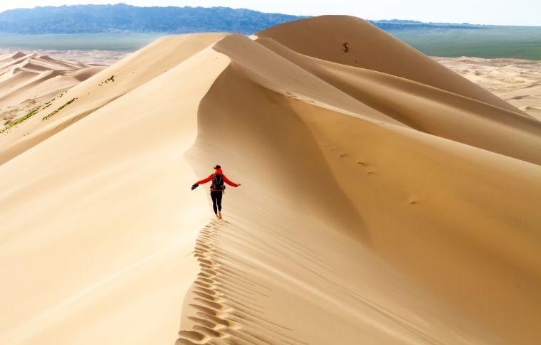traveler walking on the crest of a sand dune in the gobi desert
